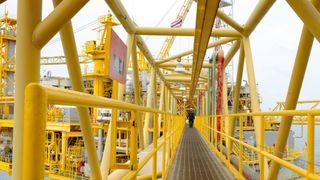 Et person sett på avstand går over bro på en oljeplattform