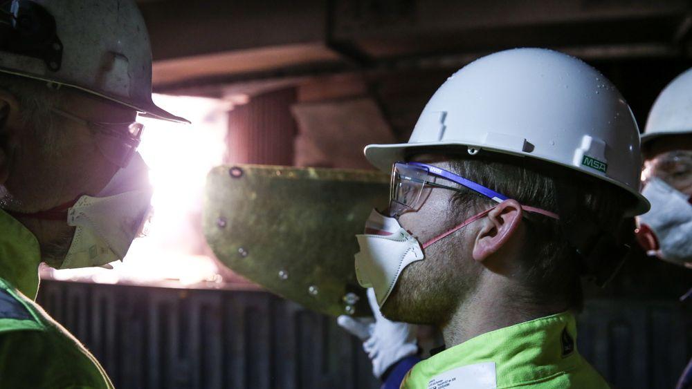 Det er strenge sikkerhetsrutiner for å komme inn til ovn 5. Her er klima- og miljøvernminister Sveinung Rotevatn inne og ser på ovnen der flytende silisium renner ned som følge av smelting i ekstrem varme.