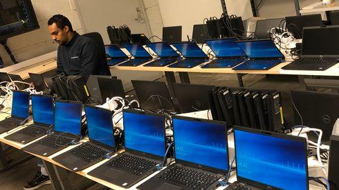 Én mann arbeider på en laptop mens flere titalls flere maskiner står på rekke og rad og venter på å bli gjort klar.