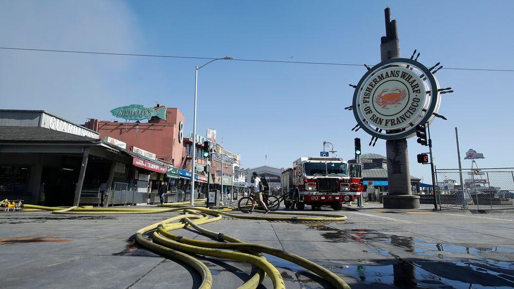 Brannslanger i gaten utenfor Fisherman's Wharf i San Francisco. En storbrann herjet lørdag Pier 45.