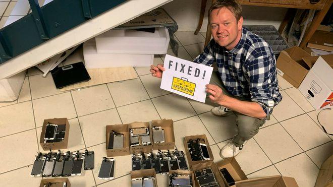 """Henrik Huseby sitter på huk med flere mobiltelefoner på gulvet rundt seg, og et skilt i hendene hvor det står """"Fixed!"""""""