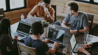 Flere personer rundt et bord, jobber på hver sin PC.
