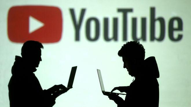 Silhuetter av to PC-brukere foran en Youtube-logo.