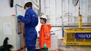 To personer i arbeidsklær på båt ser på måleinstrumenter