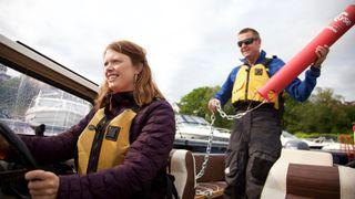 Ane Marte Hausken foran ved roret i en båt, og Torbjørn Nilsen bak i båten med en badetass i hendene.