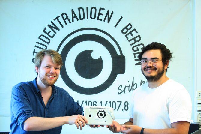 """Avtroppende redaktør Tarjei Elias Valle Kvamme (t.v.) overrekker """"Studentradioen"""" til ny redaktør Michael Breien."""