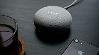 En Google Home-enhet ved siden av en Apple-mobiltelefon.