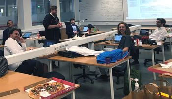 Seks av deltakerne sitter spredt rundt i et klasserom og smiler til kameraet. Rundt omkring står Peppes-esker og brusbegre.