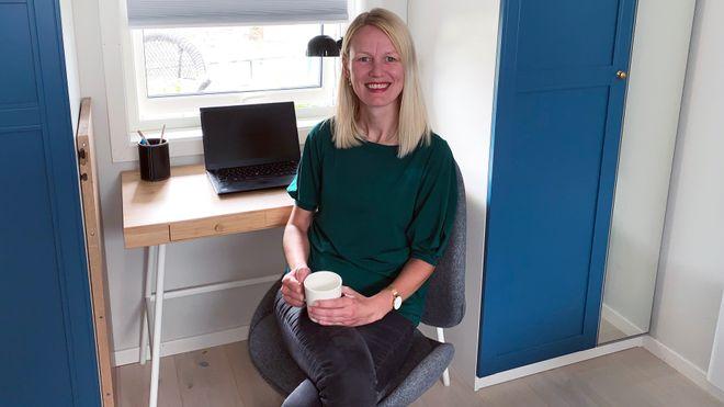 Kjersti sitter i kontorstolen med en liten pult med laptop bak seg. Hun har en kaffekopp i hånden og smiler til kamera.