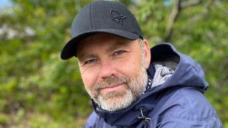 Ken Roar Riis ute i naturen med caps og allværsjakke.