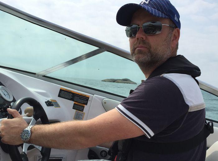 Ken Roar Riis bak roret på en båt.