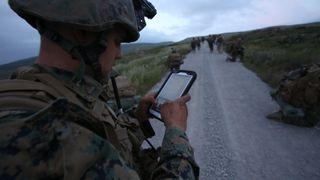 Soldat i uniform og hjelm ute i felten ser på et nettbrett.