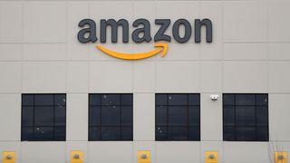 Amazon-logoen i svart og oransje på en bygning med svarte og oransje detaljer.