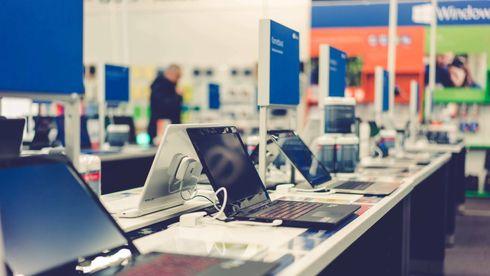 Bilde fra en Elkjøp-butikk, med PC-er på rekke og rad på et bord.