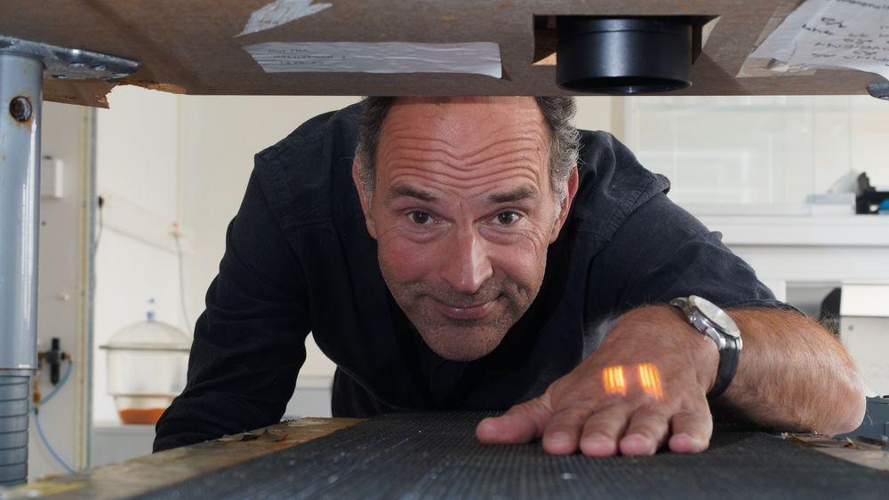 Jens Petter Wold ved en prototype på et NIR-instrument laget av Sintef Smarts Sensor Systems. Lyset sees på hånden til Wold. Dette instrumentet kan måle fettinnhold i hel laks, og tørrstoffinnhold i poteter når de passerer under sensoren.
