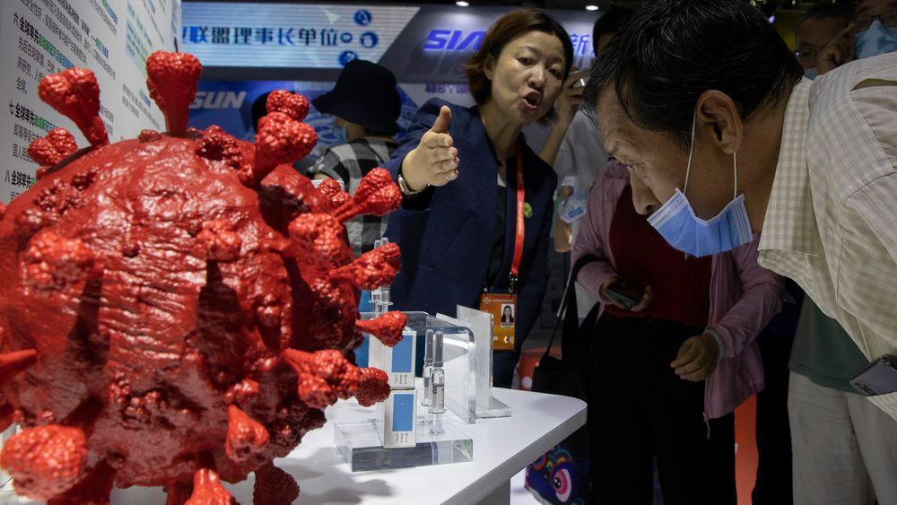 En ansatt svarer på spørsmål om koronavaksinen som utvikles av det kinesiske selskapet CNBG, under en messe i Beijing i begynnelsen av september.