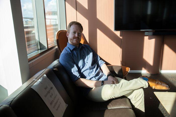 Aslak Ege sitter i en sofa på kontoret, der annet hvert sete er sperret av hensyn til smittevern.