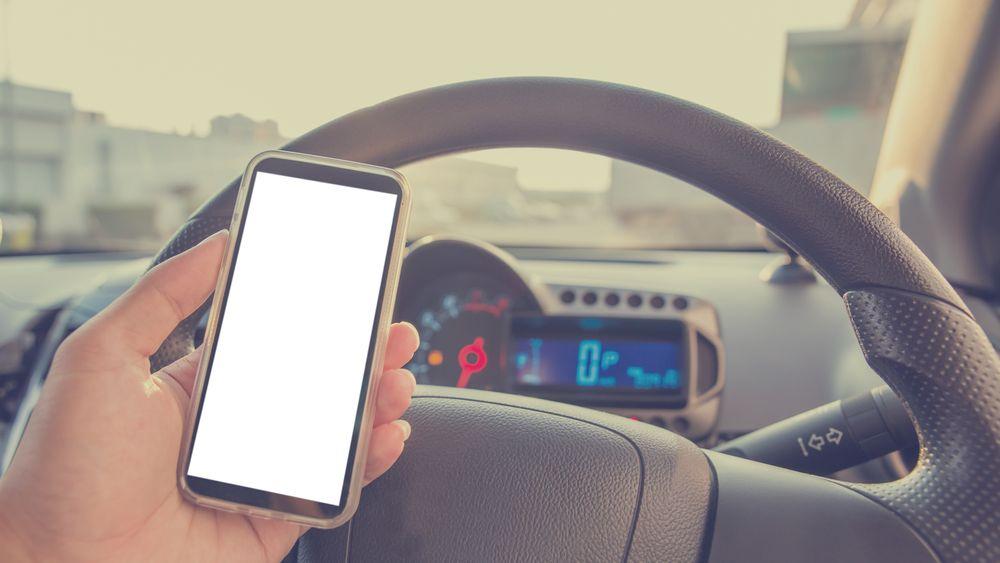 Høyesterett: Mobiltitting ved rødt lys og i stillestående kø er ulovlig