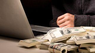 PC med masse penger ved siden av, samt hånden til en «hacker».
