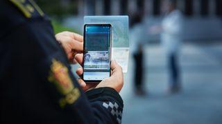 Armen til en person i politiuniform holder en telefon som tar bilde av et pass.