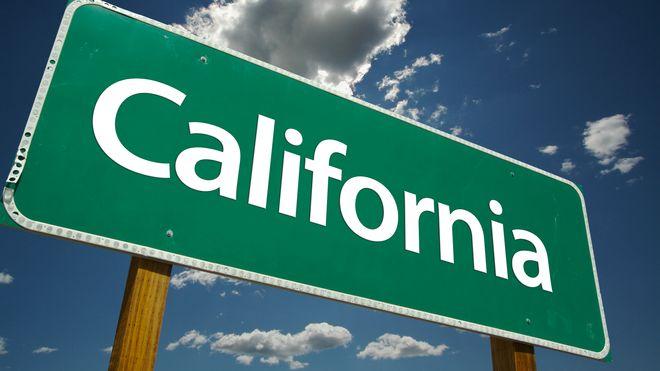 Grønt California-veiskilt med med himmelen og skyer som bakgrunn.