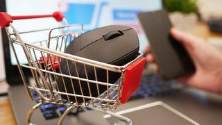 En datamus i en miniatyr-handlevogn oppå en laptop. I bakgrunnen en mobiltelefon i en hånd, og en nettbutikk-handlevogn på laptop-skjermen.