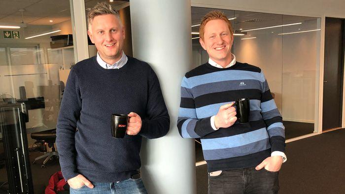 Njål A. Gjermundshaug og Stian Tonaas Fauske, med hver sin kaffekopp i hånda, smiler til kamera.