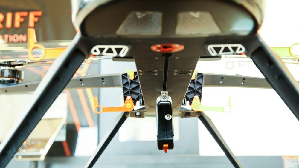 Her ser vi cargofestet er montert på dronen. I den oransje karabinkroken kan det henges gods. Kroken kan utløses av pilotene på bakken.