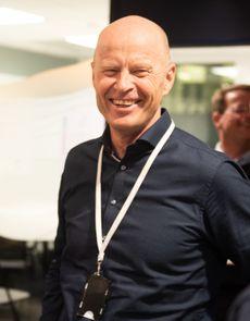 Per Gunnar Tronsli i midten av bildet, leende, med en mann med ryggen til kameraet på hver side.