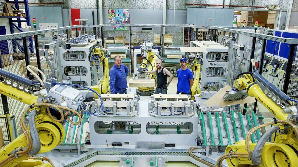 I denne robotcellen utfører fem roboter ulike arbeidsoppgaver i prosessen med å produsere armlener til Ekornes-sofaer. Den menneskelige innsatsen er å styre robotene. Fra venstre fabrikksjef Knut Ove Rygg, operatør Tore Lødøen og forbedringsleder Bruce Thurman Faulk.