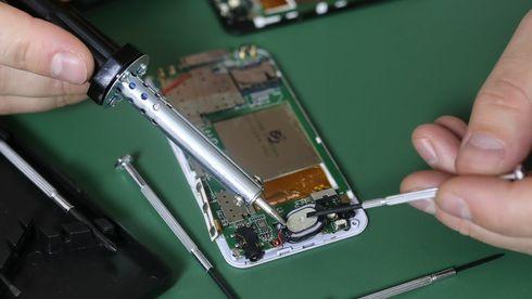 Person reparerer en mobiltelefon.