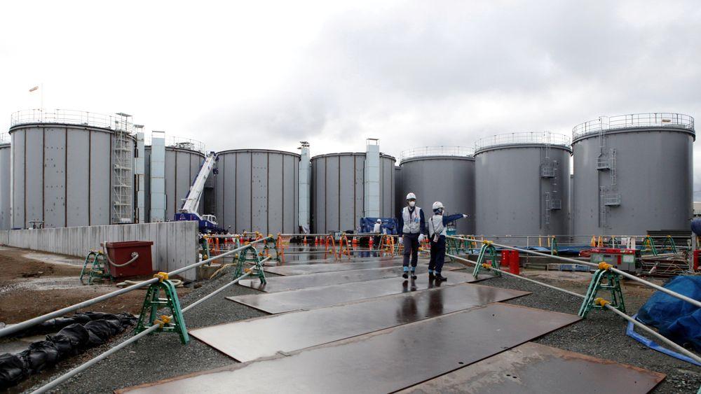 Arbeidere på kjernekraftverket Fukushima Daiichi, som eies av Tokyo Electric Power. Arbeidet med å avvikle det ødelagte atomkraftverket pågår. I bakgrunnen står tankene med radioaktivt vann.