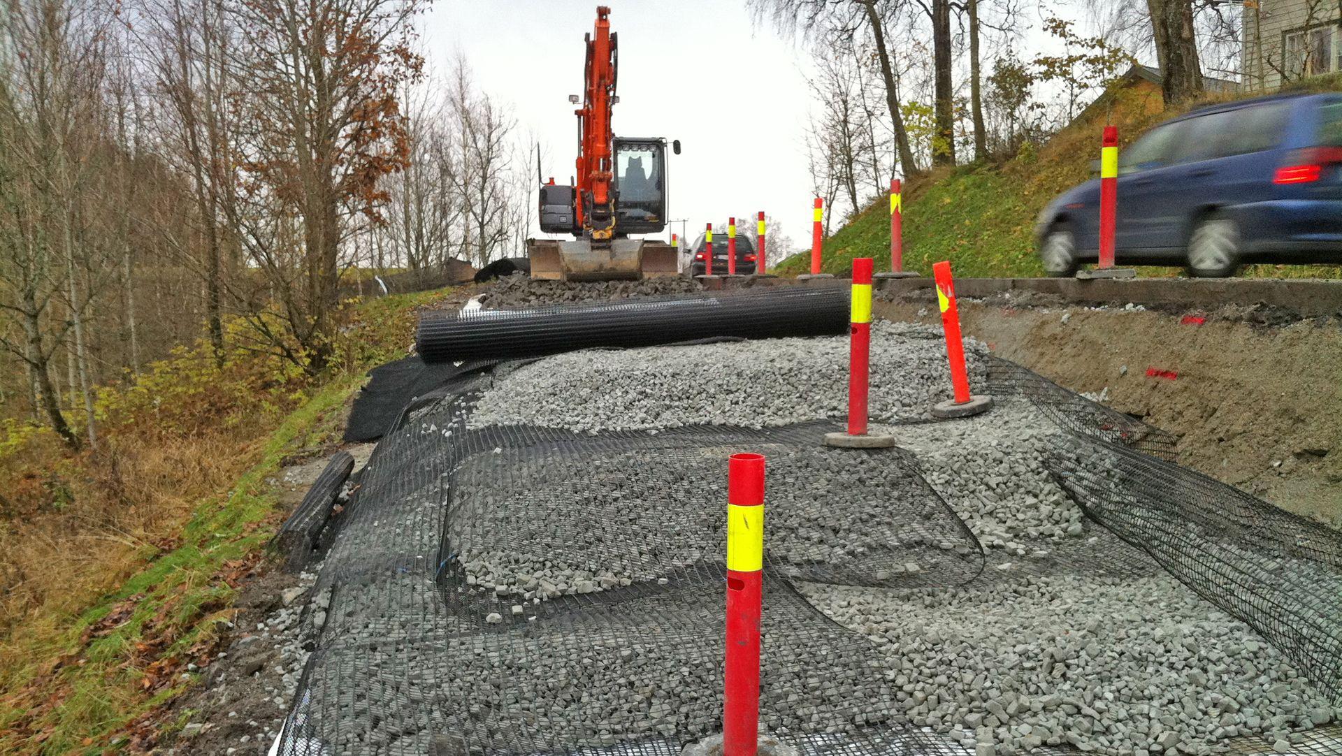 Her ser man hvordan Glasopor og geonett bygges lagvis på den siden av veien som vender ut mot skråningen samtidig som trafikken kan passere på indre felt