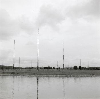 De tre første 122-metersmastene ved Jeløy Radio sett fra Gullholmsundet. Bildet er fra før 1956, da nordfløyen ble bygget og den fjerde store masten ble reist.