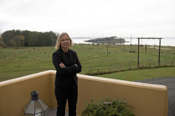 Kirsti Albert, hotelldirektør ved Jeløy Radio, foran en skog av antennemaster.
