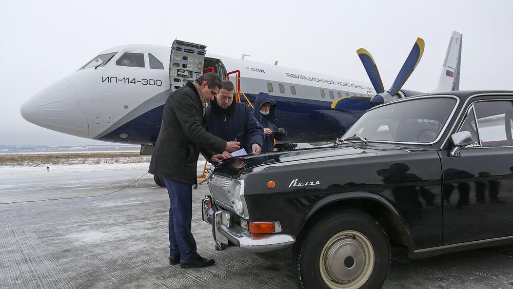Panseret på en GAZ-24 Volga brukes som skriveunderlag etter den første flygningen med Il-114-300.