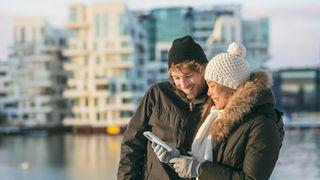 Mann og dame ser på mobiltelefonen. Ute, foran bygninger.