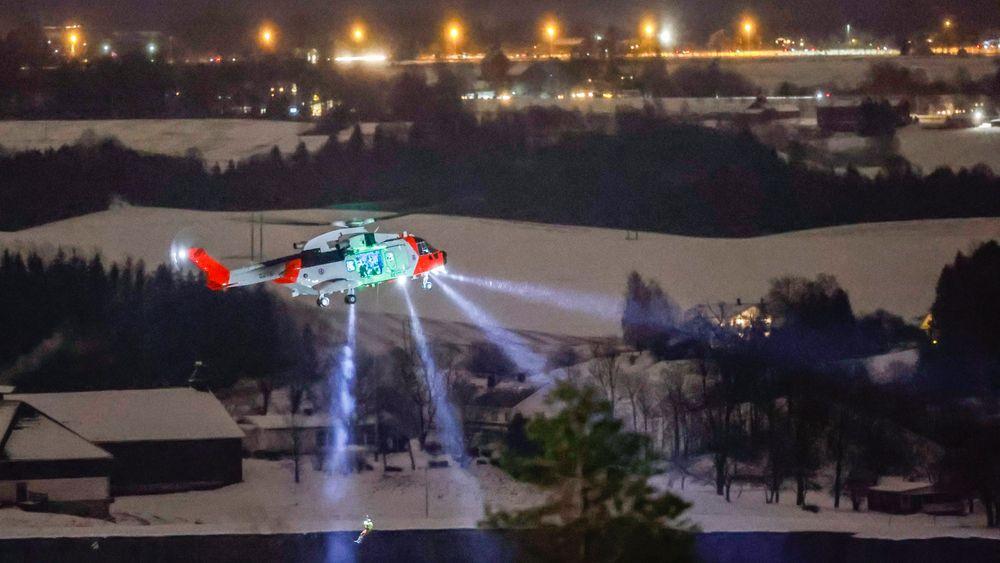 En person senkes ned fra et redningshelikopter over skredområdet i Ask onsdag kveld. Redningsarbeidet fortsetter utover natten.