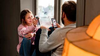 Mobiltelefoner jente og mann sitter i vinduskarm.