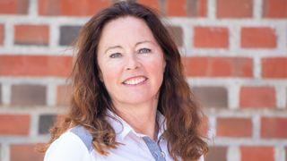Portrettfoto - kvinne med skjorte og langt brunt hår foran mursteinsvegg.