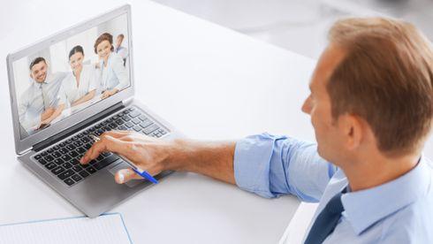 Forretningsmann som har videomøte på en bærbar PC.
