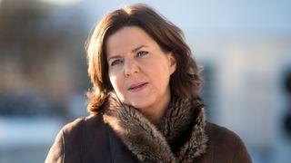 Portrettfoto av Bjurstrøm utendørs i kåpe med (fuske)pelskant.