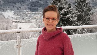 Kvinne med kort hår og briller utendørs i rosa strikkegenser.