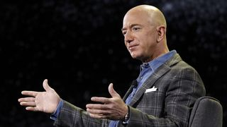 Amazon-sjef Jeff Bezos. Mann i jakke og blå skjorte som gestikulerer med armene.