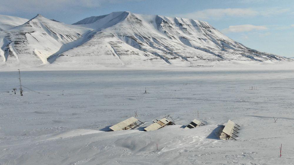 Feltforsøk på Svalbard undersøker potensialet og utfordringer for bakkemonterte solkraftverk. Her ser vi anlegget tidlig på våren når strømproduksjonen akkurat har begynt. Én rad er delvis begravd i snøfonner.