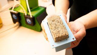 Blandingen av bakterier og sand i formen mates med finmalt kalkstein som løses opp delvis av en annen type bakterie, samt en løsning som inneholder urinstoff. Når de to bakteriene samarbeider dannes det kalsiumkarbonatkrystaller som holder sandpartiklene sammen. Etter tørking kan man ta små murstein ut av formen.