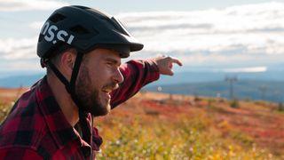 Mann med hjelm på fjell i høstfarger peker mot utsikt