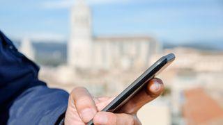 Mann med smartmobil å hånden. Katedralen i Girona, Spania, i bakgrunnen.