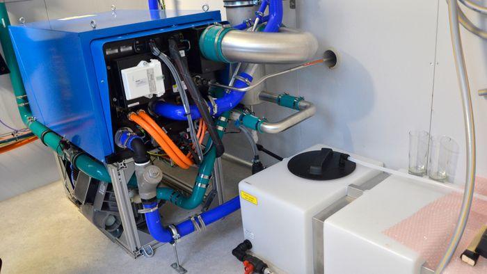 Brenselcellene som produserer strøm ligger inne i denne blå boksen, mens plastanken nederst til høyre samler opp vann som blir det eneste avfallsstoffet fra prosessen.