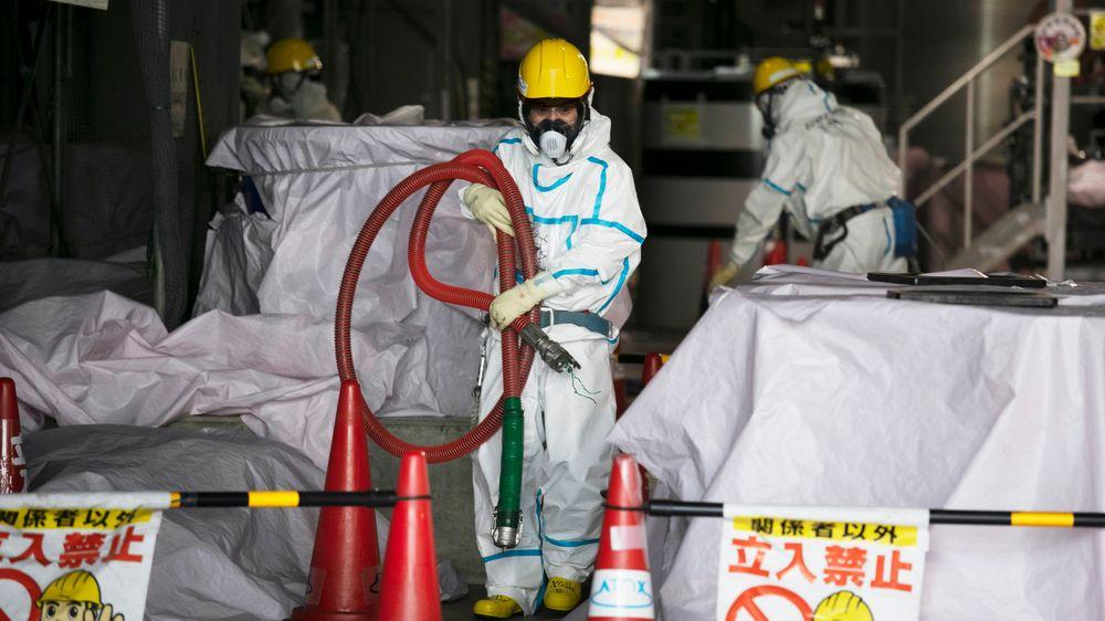 Arbeidere med beskyttelsesdresser jobber ved den ødelagte atomkraftverket Fukushima Daiichi i Japan. Arbeidet med å rydde opp og avvikle atomkraftverket etter katastrofen vil ta 30–40 år og koste enorme beløp.